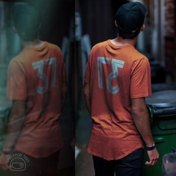 The number 37, reversed, roller ink effect, on orange t-shirt, on model, back